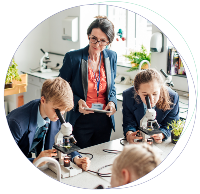 A woman standing near students who observe a plant with microscopes.