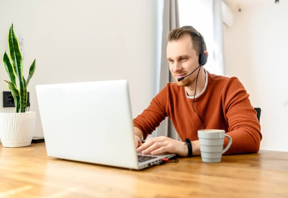 Young man uses handsfree headset to work from home