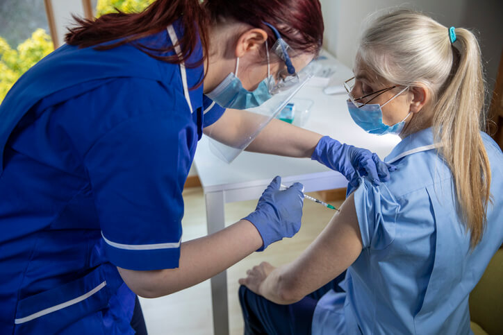 A young female nurse gives a colleague a vaccination against Covid 19